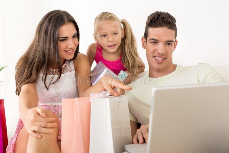 Gelukkige familie die online het winkelen hebben stock foto
