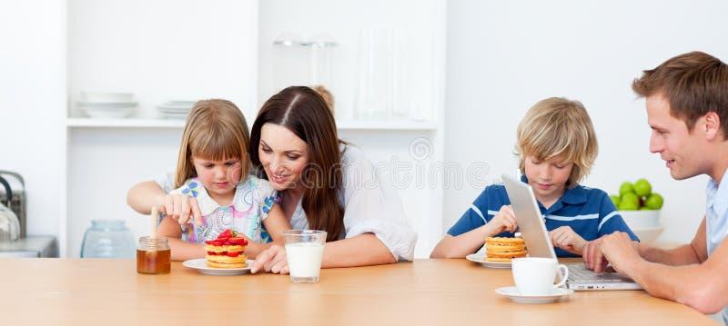Gelukkige familie die ontbijt in de keuken eet stock afbeeldingen