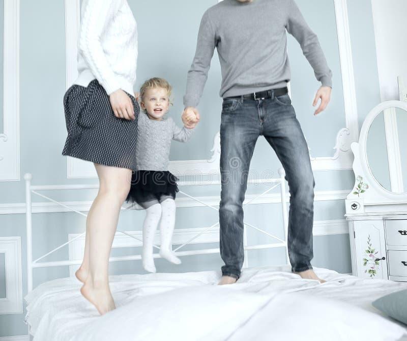 Gelukkige familie die op bed samen springen en pret hebben stock afbeeldingen
