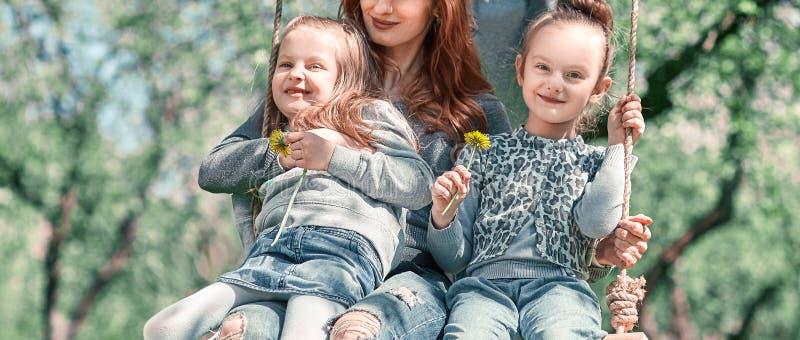 Gelukkige familie die op de tuinschommeling slingeren op een de zomerdag royalty-vrije stock afbeelding