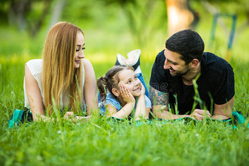 Gelukkige familie die op gras in de zomerpark liggen De jonge dochter bekijkt vader stock foto's