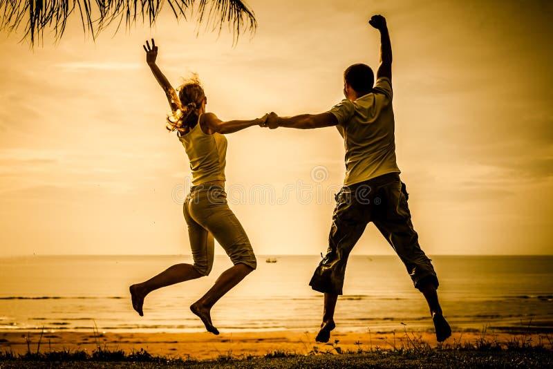 Gelukkige familie die op het strand op de dageraadtijd springen royalty-vrije stock foto's