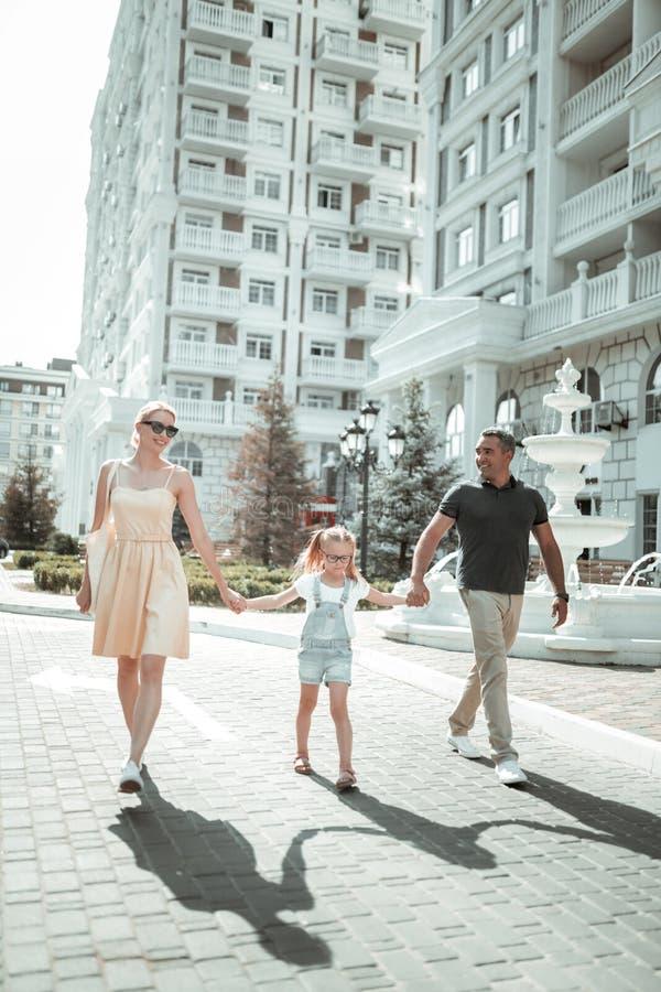 Gelukkige familie die op hun manier aan van de binnenstad lopen stock foto