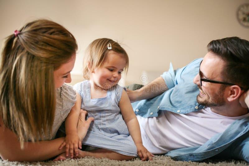 Gelukkige familie die op vloer met hun kleine baby liggen royalty-vrije stock foto's