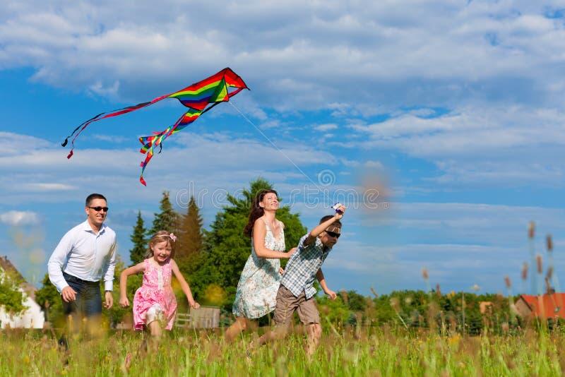 Gelukkige familie die op weide met een vlieger loopt stock afbeeldingen