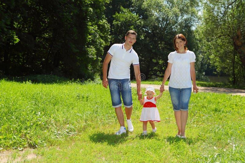 Gelukkige familie die in park loopt stock foto