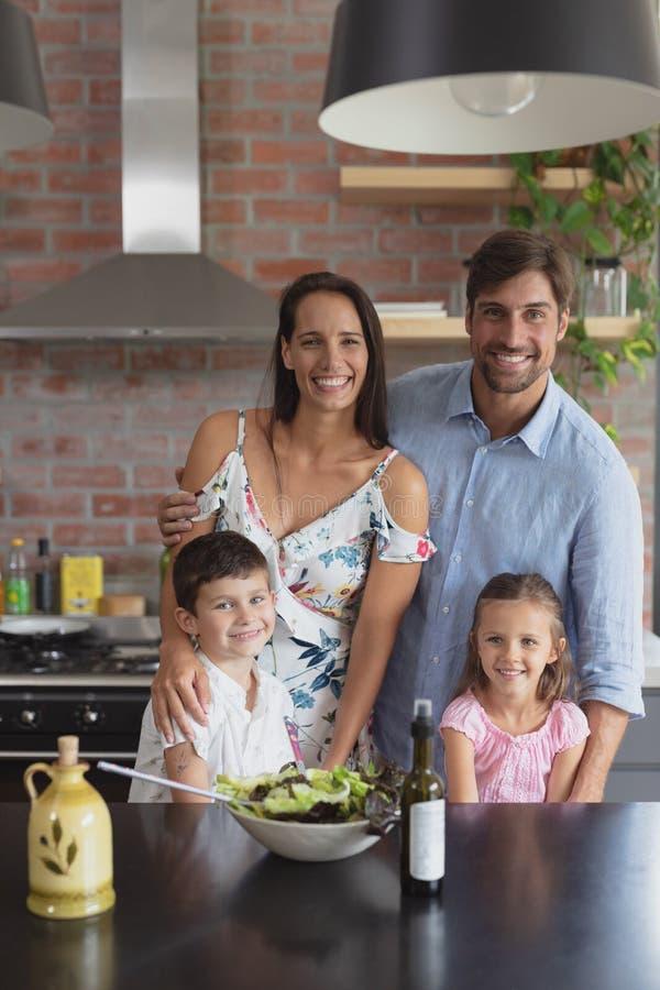 Gelukkige familie die plantaardige salade in keuken thuis voorbereiden stock foto's
