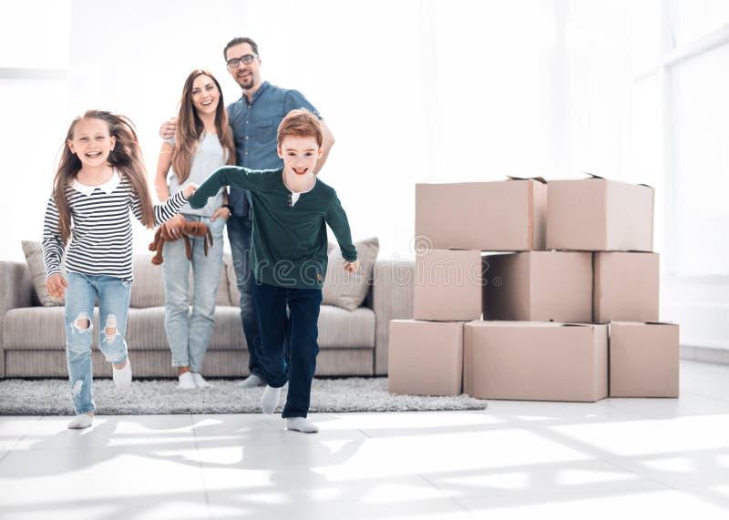 Gelukkige familie die pret in een nieuwe flat hebben royalty-vrije stock afbeelding