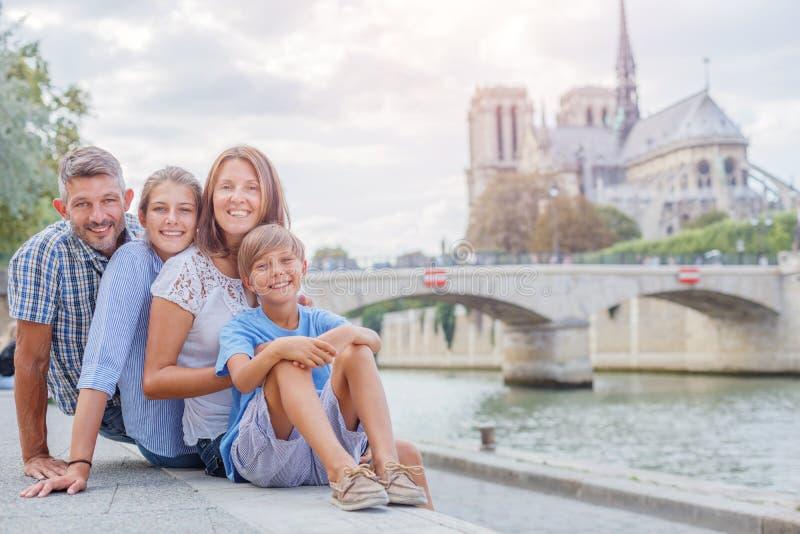 Gelukkige familie die pret hebben dichtbij Notre-Dame-kathedraal in Parijs Toeristen die van hun vakantie in Frankrijk genieten stock foto's