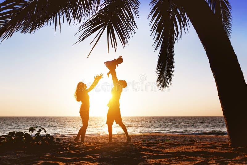 Gelukkige familie die pret hebben onder palm op zonsondergangstrand royalty-vrije stock foto's