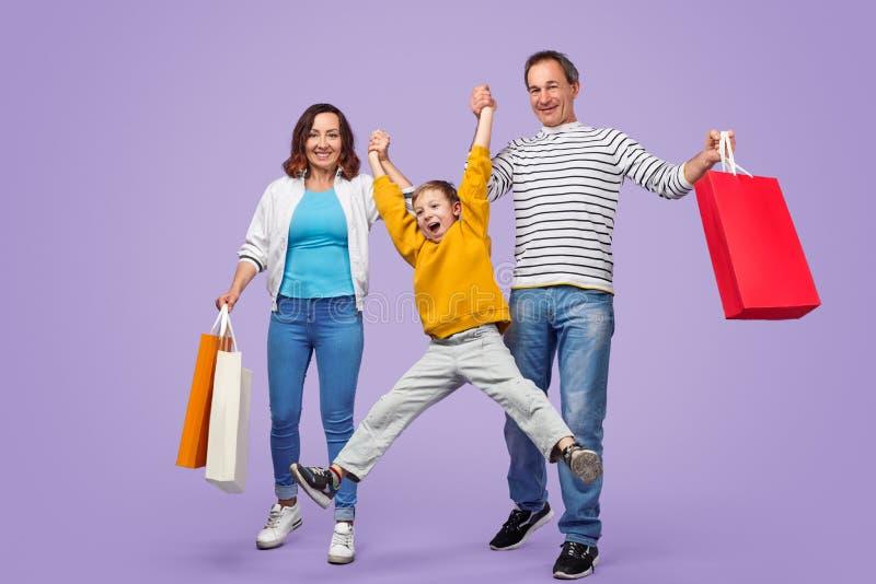 Gelukkige familie die pret hebben tijdens het winkelen stock foto