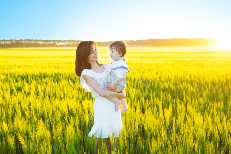 Gelukkige familie die pret heeft Babyjongen en zijn moeder die pret hebben door gebied die in openlucht van aard genieten stock foto