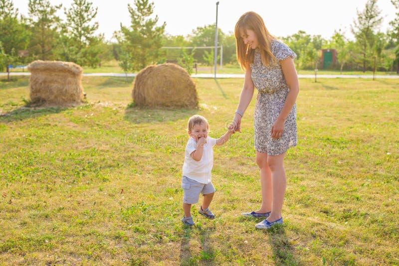 Gelukkige familie die pret heeft babyjongen en zijn moeder die in openlucht spelen stock foto