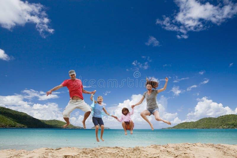 Gelukkige familie die pret heeft bij tropisch strand.