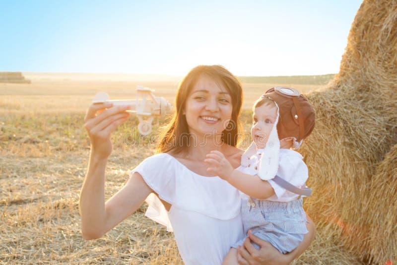 Gelukkige familie die pret heeft Gelukkige moeder en haar weinig zoon op het gebied openlucht stock afbeelding