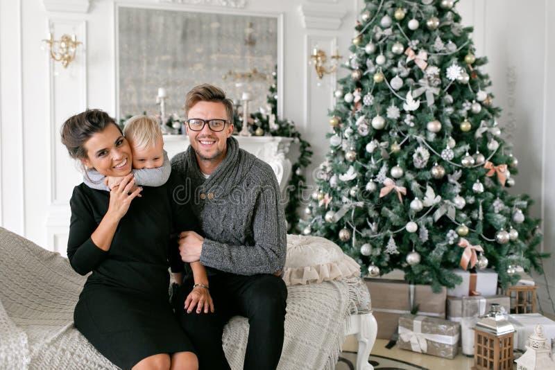 Gelukkige familie die pret heeft thuis Kerstmisochtend in heldere woonkamer Jonge ouders met weinig zoon Vader, moeder royalty-vrije stock fotografie