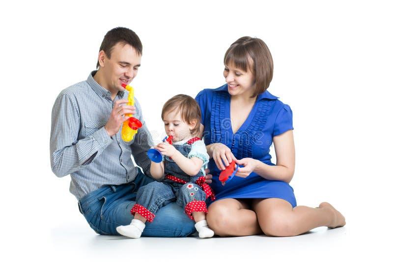 Gelukkige familie die pret met muzikaal speelgoed hebben. Geïsoleerd op witte bac royalty-vrije stock foto