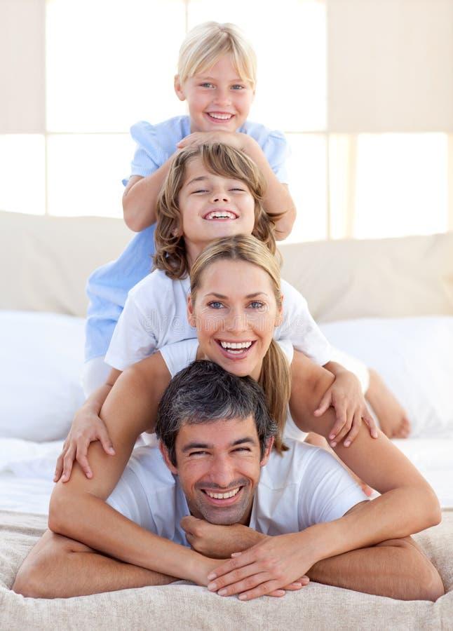 Gelukkige familie die pret op een bed heeft stock foto's