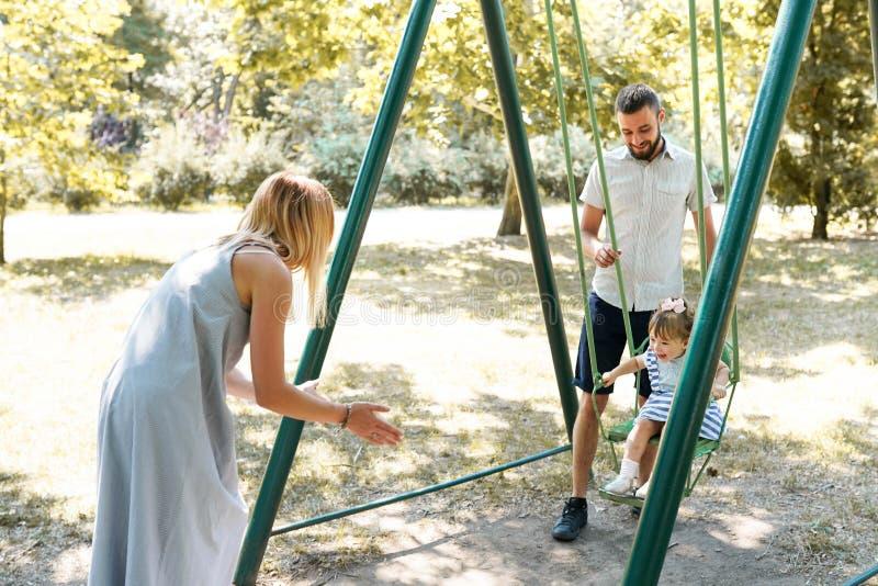 Gelukkige familie die pret op een schommelingsrit hebben bij een tuin een de zomerdag royalty-vrije stock afbeeldingen