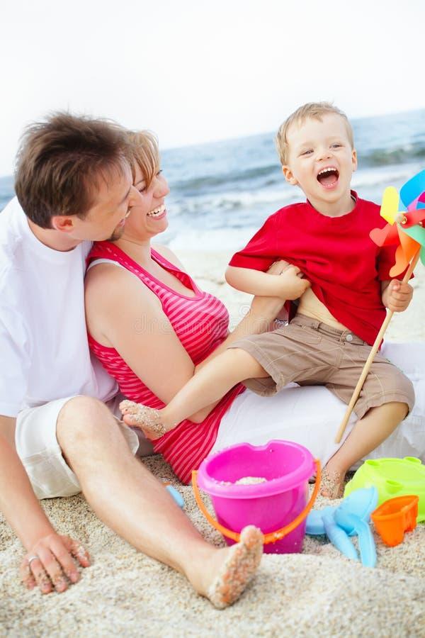 Gelukkige familie die pret op het strand heeft. royalty-vrije stock afbeelding