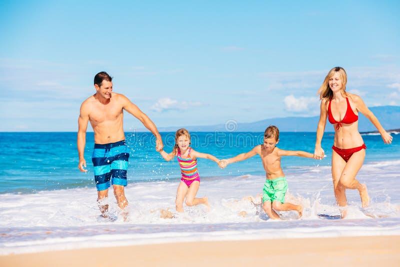 Gelukkige familie die pret op het strand heeft stock foto