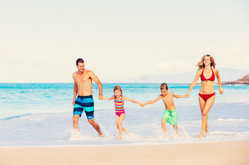 Gelukkige familie die pret op het strand heeft stock fotografie