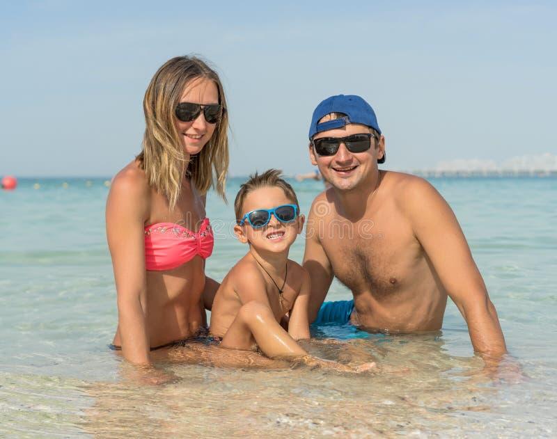 Gelukkige familie die pret op tropisch wit strand hebben Moeder, vader, een leuke zoon Positieve menselijke emoties, gevoel, vreu royalty-vrije stock fotografie