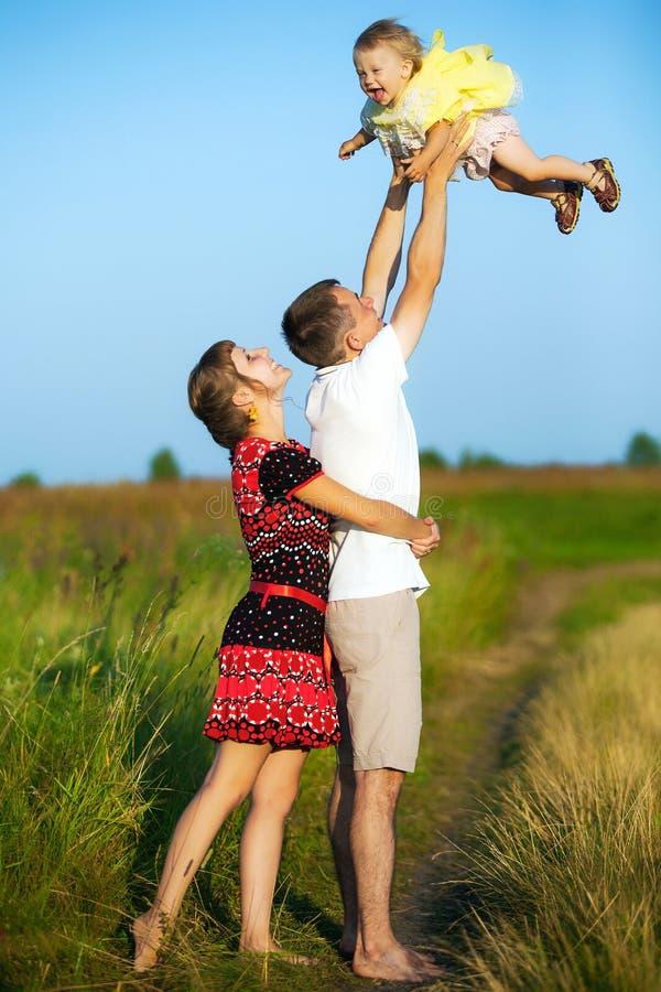 Gelukkige familie die pret in openlucht in de zomerweide hebben royalty-vrije stock afbeelding