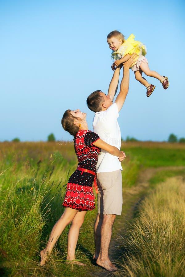 Gelukkige familie die pret in openlucht in de zomerweide hebben stock foto