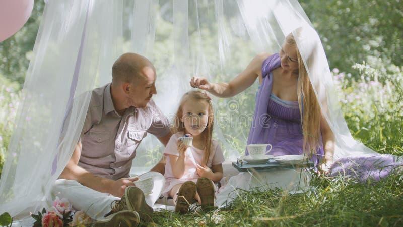 Gelukkige familie die pret in openlucht in groen park hebben - moeder, vader en dochter royalty-vrije stock foto