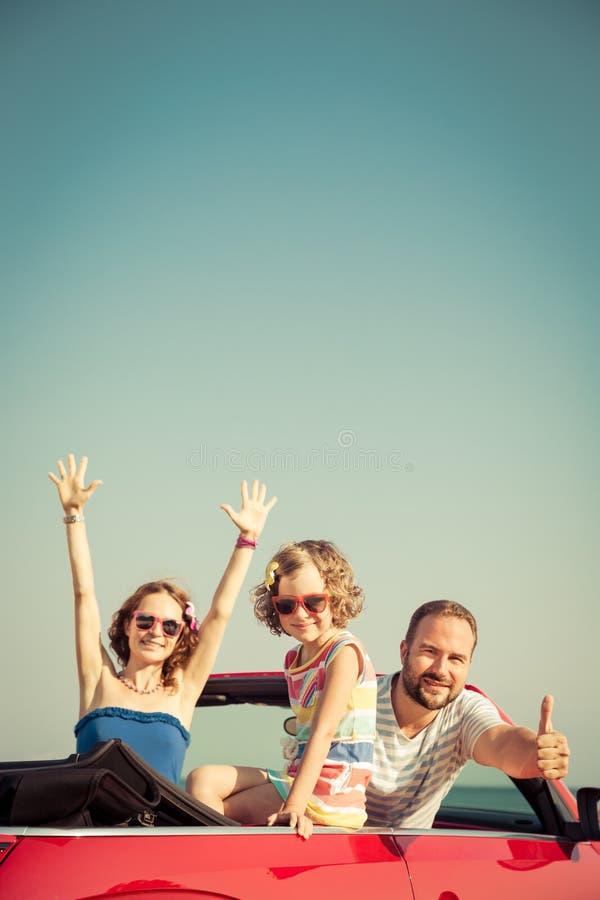 Gelukkige familie die pret in rode cabriolet hebben stock afbeelding