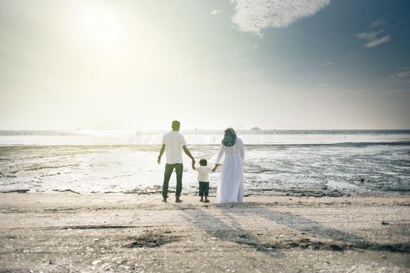 Gelukkige familie die prettijd hebben samen bij het strand die aardige die zonsondergangmening hebben in Pantai Remis wordt geves royalty-vrije stock foto