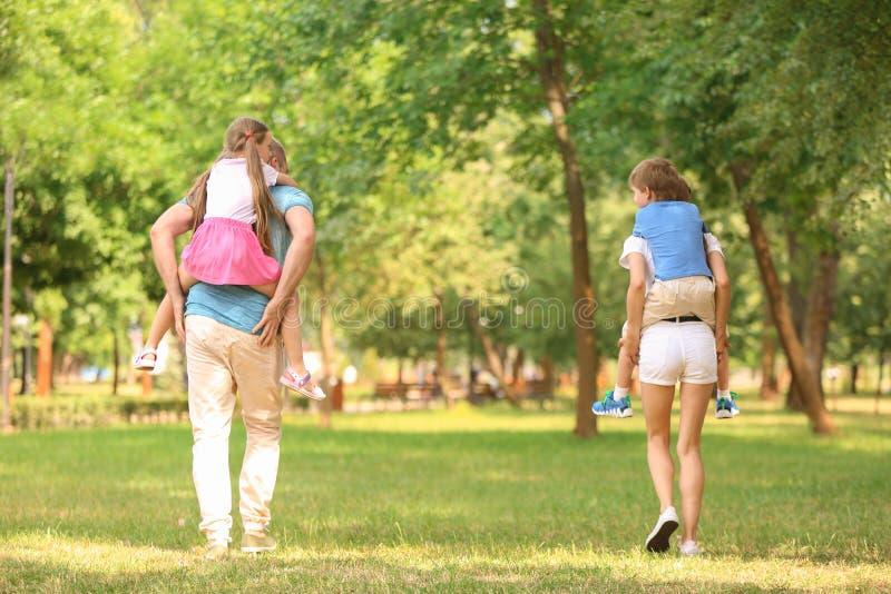 Gelukkige familie die samen in groen park lopen stock foto's