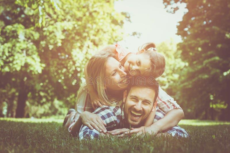 Gelukkige familie die samen van in de zomerdag genieten Familie die op gr. liggen stock afbeelding