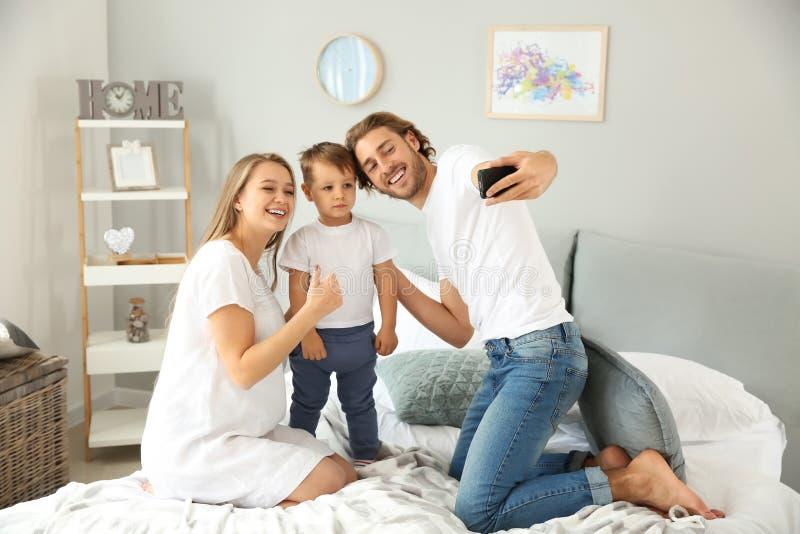 Gelukkige familie die selfie in slaapkamer nemen stock foto's