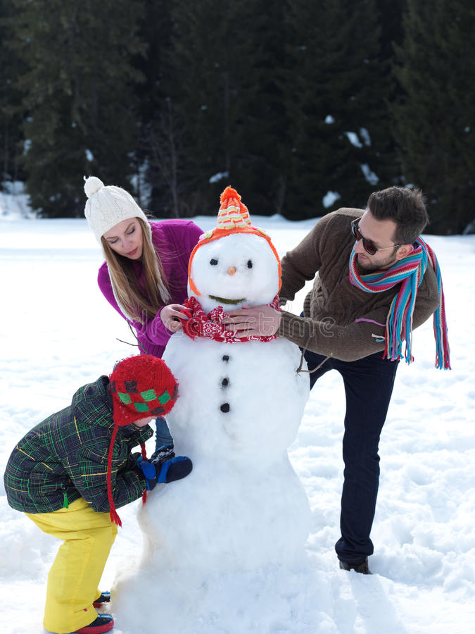 Gelukkige familie die sneeuwman maakt stock fotografie