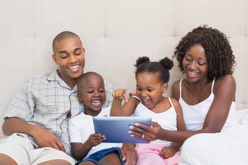 Gelukkige familie die tablet samen op bed gebruiken royalty-vrije stock foto's