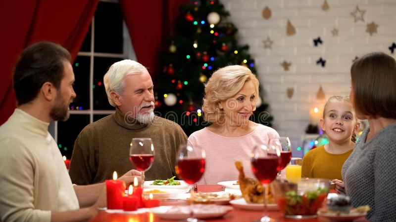 Gelukkige familie die traditioneel Kerstmisdiner, meisje hebben die grappige verhalen vertellen stock afbeeldingen