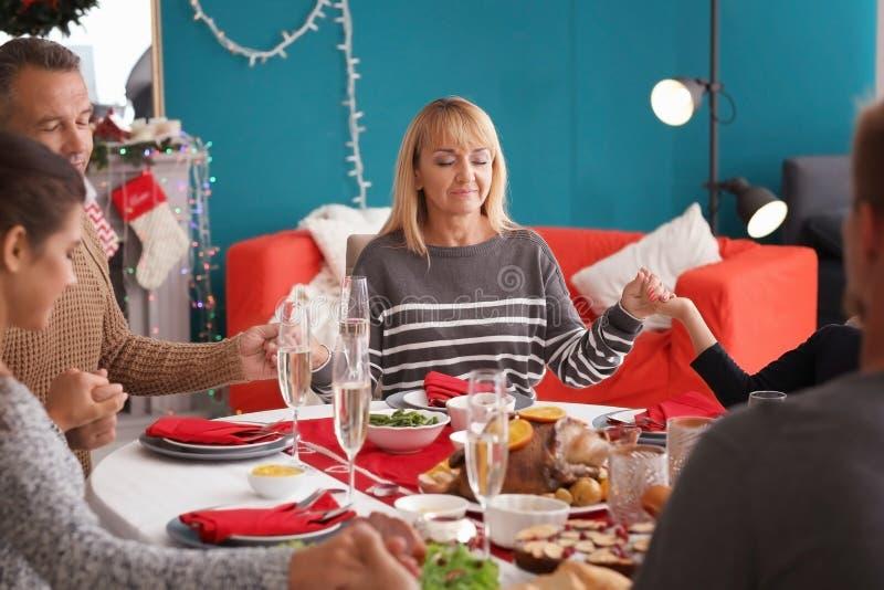 Gelukkige familie die vóór het hebben van Kerstmisdiner thuis bidden royalty-vrije stock afbeelding