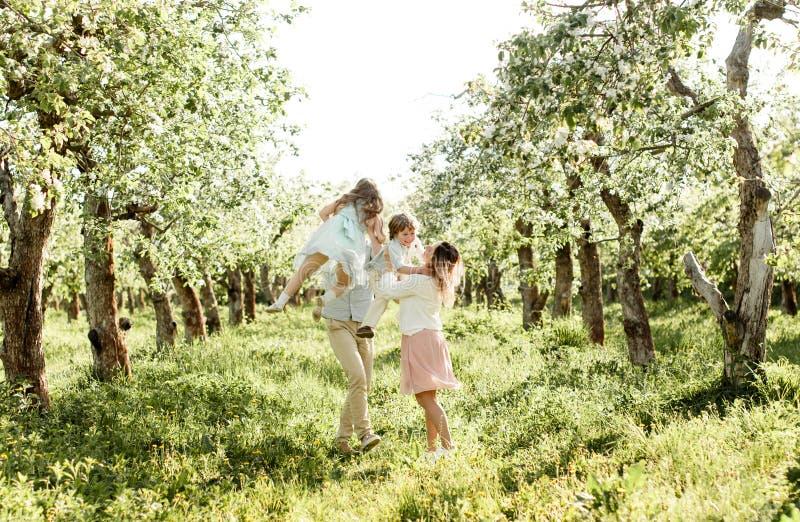Gelukkige familie die van de lente genieten samen bij appelboomgaard royalty-vrije stock foto's