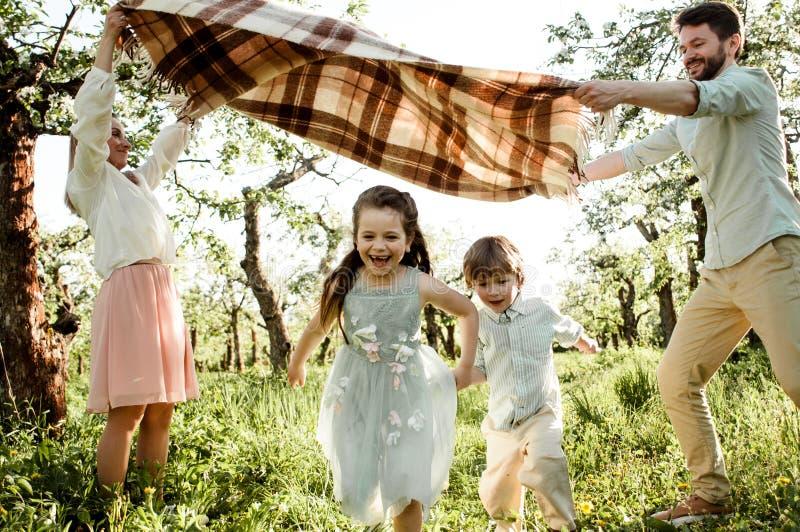 Gelukkige familie die van de lente genieten samen bij appelboomgaard stock afbeeldingen