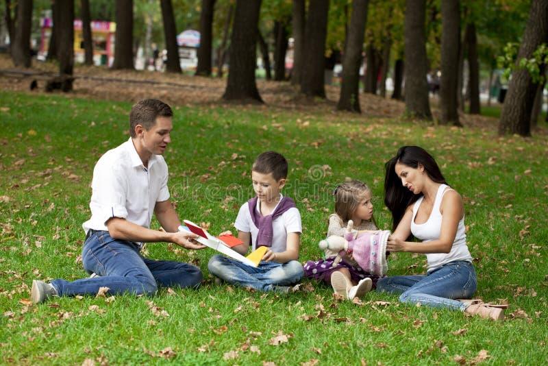 Gelukkige familie die van vier, in het de herfstpark rusten stock foto