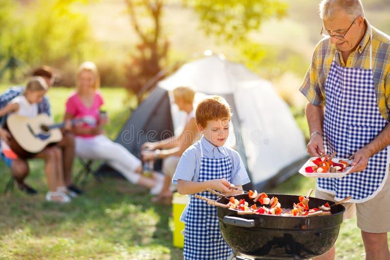 Gelukkige familie die vlees op een barbecue roosteren stock foto's