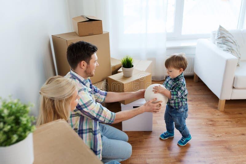 Gelukkige familie die zich aan nieuwe huis en het spelen bal bewegen royalty-vrije stock foto's