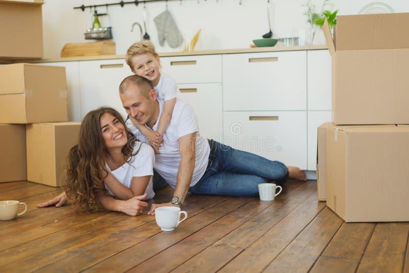 Gelukkige familie die zich naar huis met rond dozen bewegen royalty-vrije stock afbeelding