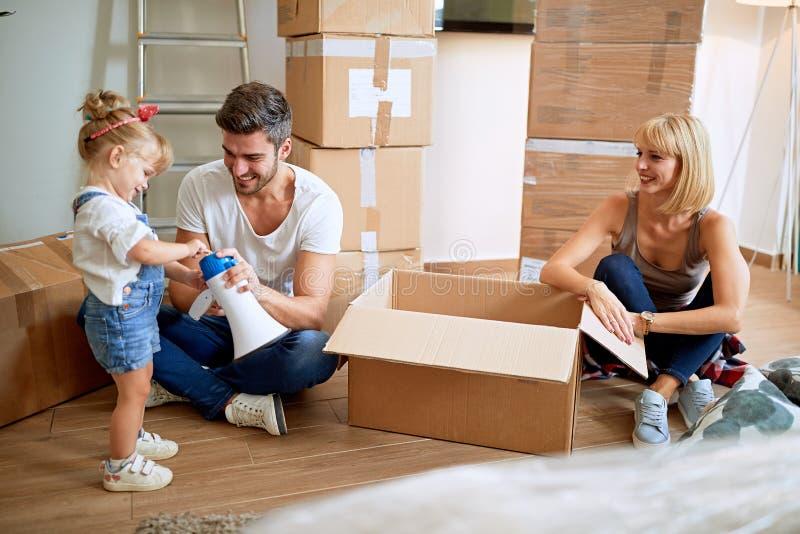 Gelukkige familie die zich in nieuwe huis uitpakkende dozen bewegen royalty-vrije stock afbeelding