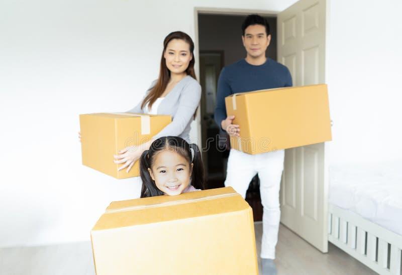 Gelukkige familie dragende dozen in nieuw huis bij het bewegen van dag op vage achtergrond Bewegend concept royalty-vrije stock afbeelding