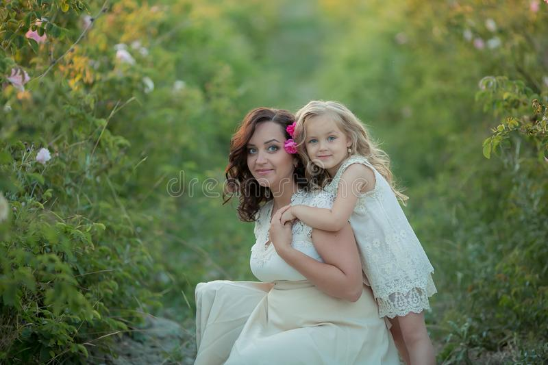 Gelukkige familie: een jonge mooie zwangere vrouw met haar weinig leuke dochter die op het tarwe oranje gebied lopen op a stock afbeelding
