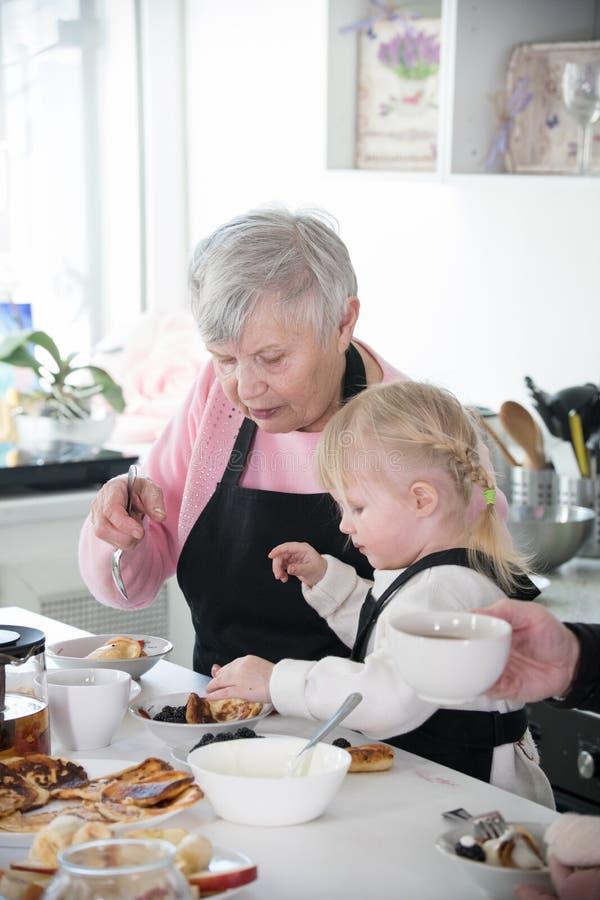Gelukkige Familie Een klein meisje en haar grootmoeder het koken in de keuken stock afbeelding