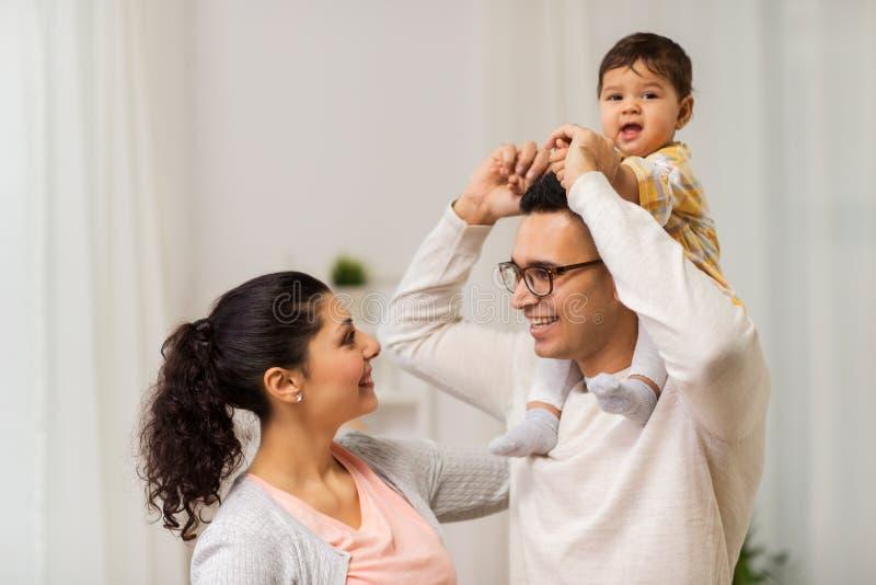 Gelukkige familie en babydochter die thuis spelen stock afbeelding